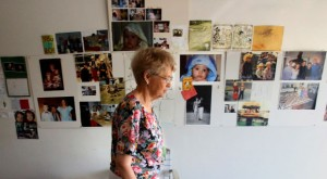 Client Stella Brown walks past her wall of memories on her way with Volunteer Mary Keller